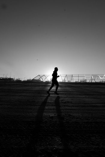 Silhouette Person Jogging On Field Against Sky During Sunset