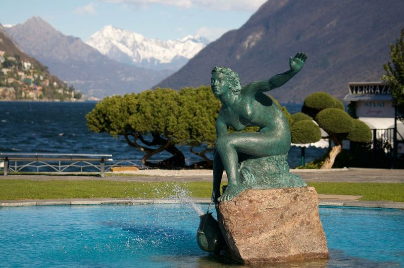 Statue in lake with mountain range in background
