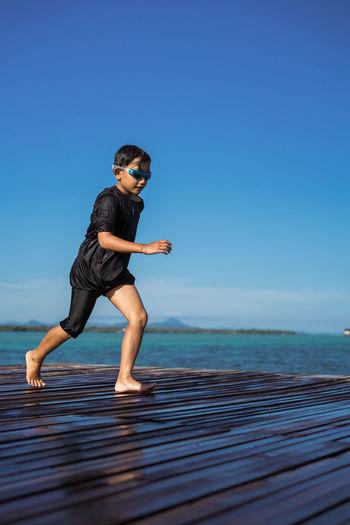 Full length of boy running on pier over sea against blue sky