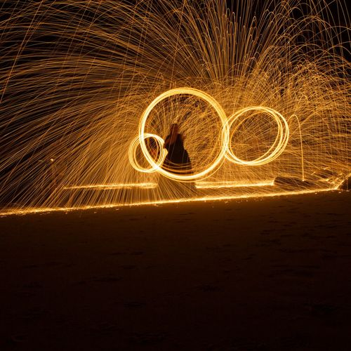 Silhouette Person Making Light Painting At Night