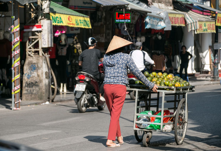 Vietnam Hanoi Hanoi Vietnam  Hat Working Woman Business Street Business Streetphotography Street Photography Street On The Road On The Street Real People Transportation City Mode Of Transportation Retail  People Women Rear View Day Incidental People Outdoors
