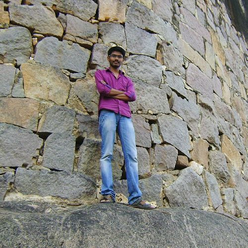Full Length Of Young Man With Arms Crossed Standing Against Stone Wall