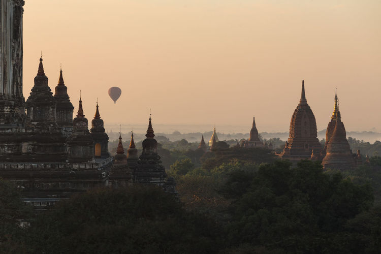 Hot air balloons flying over temple against sky