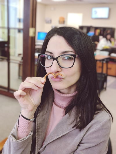 Portrait of woman holding pretzel at restaurant