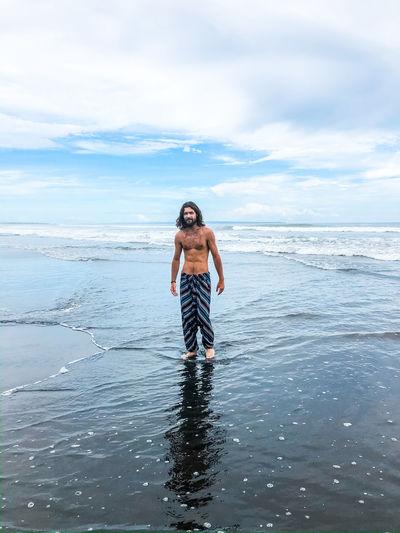Full length of shirtless man standing in sea against sky