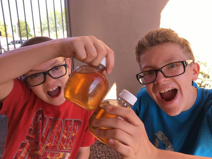 Cheers to apple juice! Boys Brothers Siblings Kids Apple Juice Bottles Apple Juice Drinking Cheers Joy Joyful Friendship Eyeglasses  Togetherness Smiling Portrait Drink Happiness