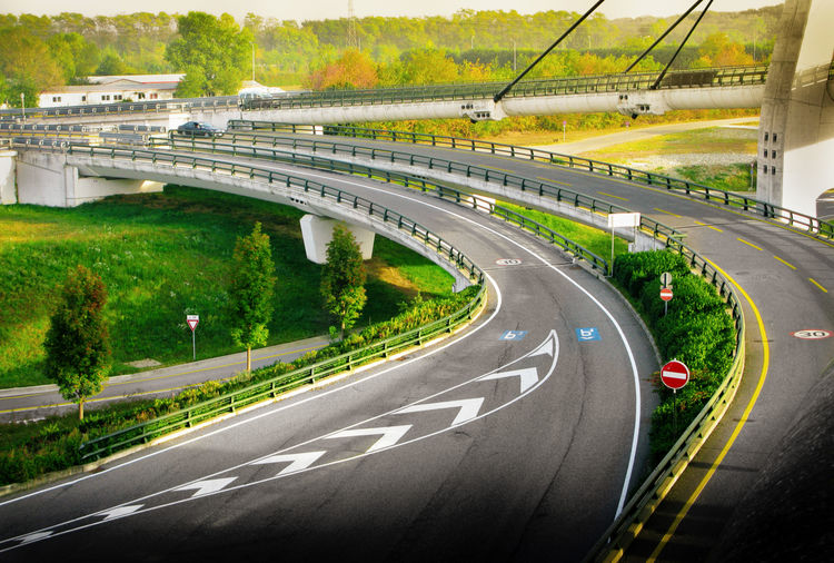 Road Transportation Sign Highway Symbol Direction Architecture Plant Mode Of Transportation Road Marking No People Marking Motor Vehicle Motion Curve City Connection Car Built Structure The Way Forward Multiple Lane Highway Outdoors Dividing Line Overpass