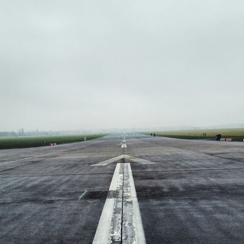 Markings on airport runway against clear sky
