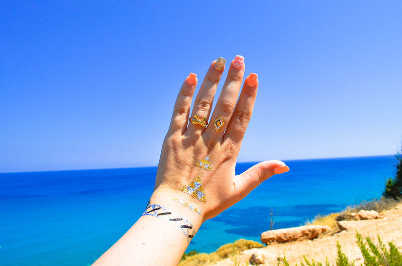 Cropped hand with temporary tattoo in front of sea