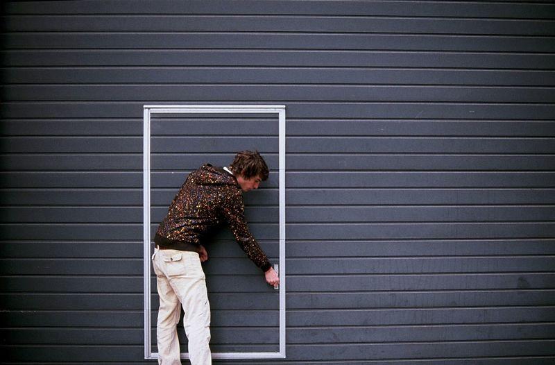 Full Length Of Young Man Opening Door
