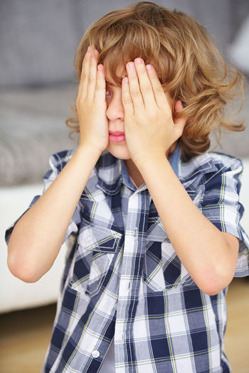 Close-up of boy with hands covering face sitting at home