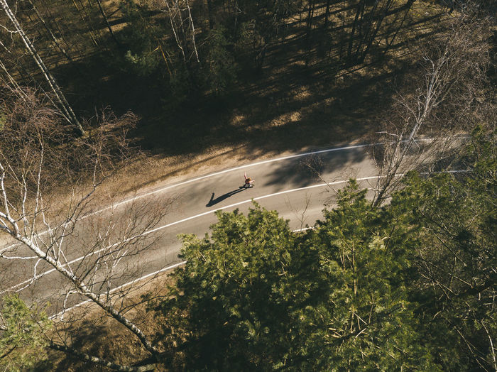 Aerial view of woman skateboarding on road amidst trees