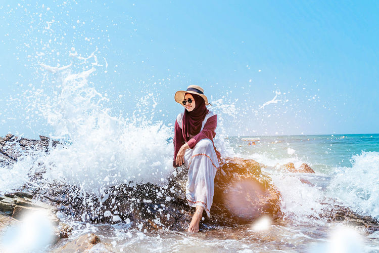 confident young muslim asian woman sitting on rock with beautiful wave splash background . woman sitting on cliff over sea. Travel concept. Water Sea Motion Splashing One Person Leisure Activity Young Adult Sport Adult Nature Women Hat Sky Lifestyles Enjoyment Sunlight Beach Horizon Over Water Outdoors Muslim Islam Arab ASIA Malaysia INDONESIA Hijab Travel Destinations Blue Summer Vacations Happy Relaxing Freedom People Wave