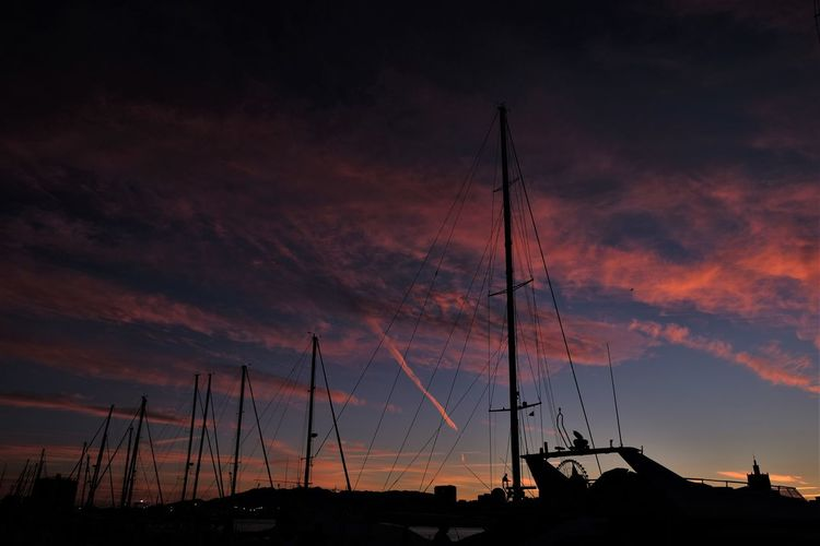 Silhouette sailboats moored at harbor against sky during sunset