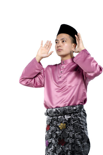 Portrait of young and handsome asian man with traditional clothing during hari raya over white background Studio Shot White Background Indoors  One Person Front View Standing Cut Out Gesturing Women Looking Clothing Copy Space Young Adult Casual Clothing Three Quarter Length Females Portrait Young Women Human Arm Arms Raised Isolated