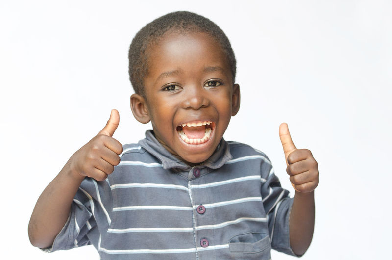 Portrait of smiling boy standing against white background