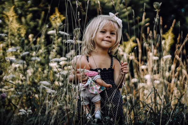 Portrait of innocent girl holding doll amidst plants on field