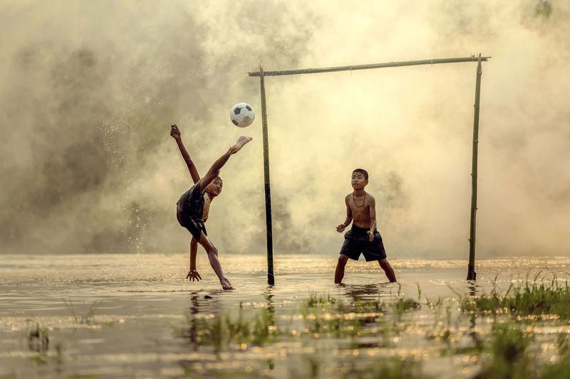 Boys playing soccer playing on rainy season