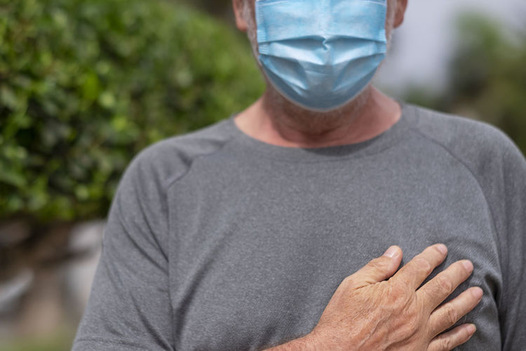 Midsection of man wearing mask standing outdoors