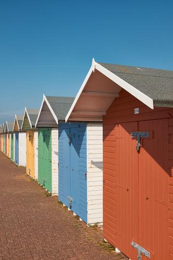 Houses on beach against clear blue sky