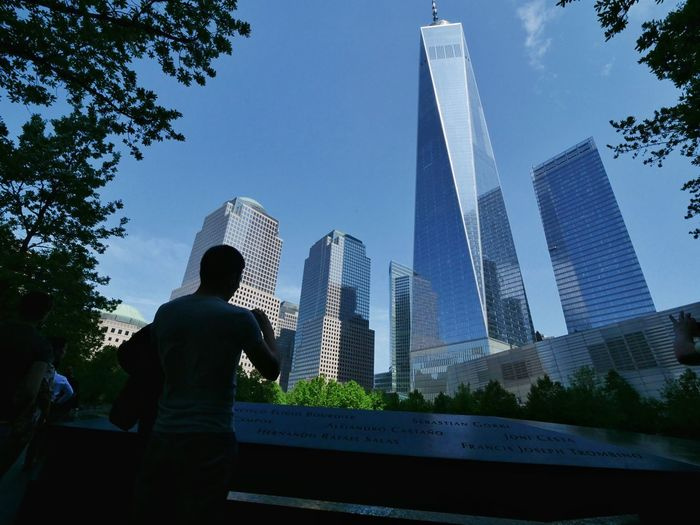 Low angle view of man standing by modern buildings against sky