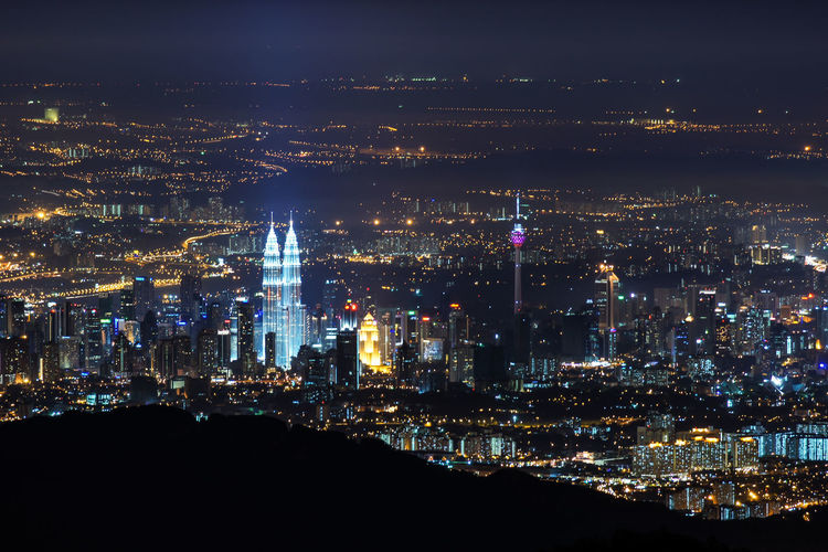 Mid distance view of illuminated petronas tower and kuala lumpur tower at night