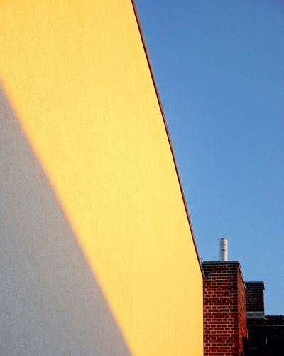 Architecture Built Structure Building Exterior No People Clear Sky Outdoors Day Low Angle View Yellow Blue Sky City Chimney Roof Rooftop Light And Shadow Shadow Fassade Minimalism