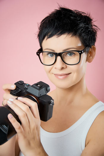 Portrait Looking At Camera One Person Headshot Smiling Front View Indoors  Eyeglasses  Close-up Real People Holding Technology Glasses Young Adult Lifestyles Camera - Photographic Equipment Young Women Photography Themes Women Beautiful Woman Camera Camera - Photographic Equipment Photographer