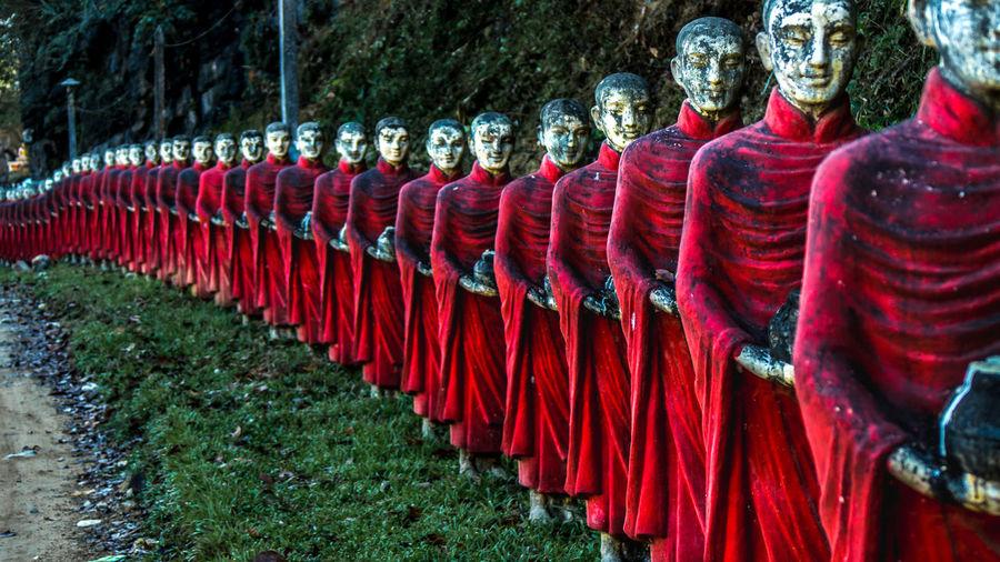 Old buddha statues on grassy field