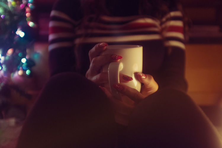 Holding One Person Adult Focus On Foreground Communication Wireless Technology Technology Indoors  Women Night Portable Information Device Illuminated Portrait Headshot Activity Photography Themes Young Adult Human Body Part Hand Christmas Christmas Lights Chrsitmastree Nail Art Cup Coffee