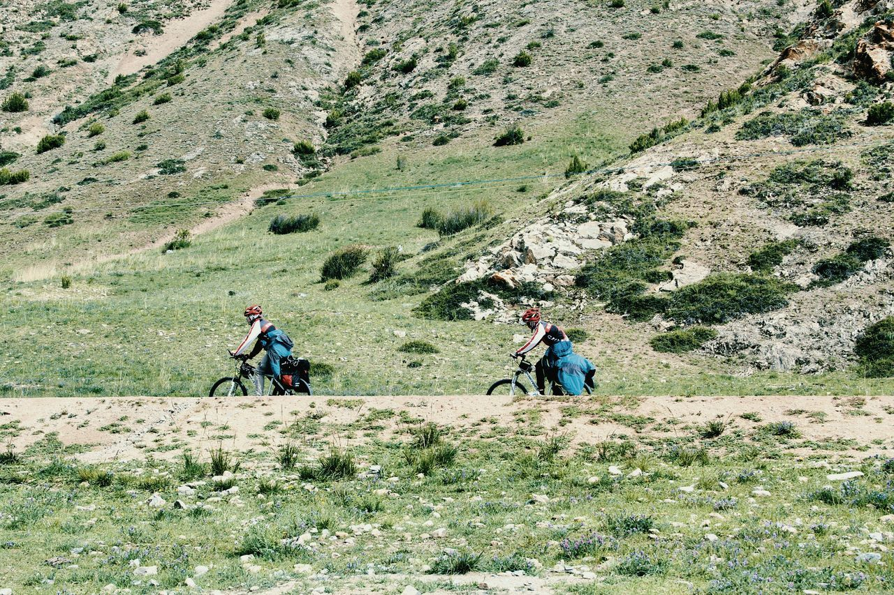 Side View Of Friends Riding Bicycle Against Mountain