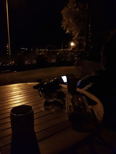 Illuminated drink on table by street in city at night