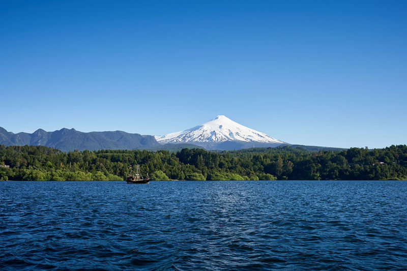 Lake and volcano Villarrica... Idyllic Copy Space Volcano Travel Destinations Day Mountain Range No People Clear Sky Sky Blue Non-urban Scene Tranquil Scene Tranquility Beauty In Nature Waterfront Mountain Scenics - Nature Mountain Peak Snowcapped Mountain Water Nature Lake Outdoors Scenics Landscape
