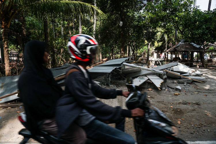Indonesia, Lombok Island West Nusa Tenggara (NTB), on Sunday (5/8/2018) at around 6:46 p.m., the earthquake with a strength reached 7.0 on the Richter Scale (SR). The photo was taken 3 days after the earthquake along the road to North Lombok which suffered the worst damage. residents make emergency tents along the main road and wait for government assistance and donations from volunteers. the situation in Lombok is still severe, making traffic jams everywhere, scrambling for help to survive. Tree Real People Plant Day People Men Two People Leisure Activity Nature Lifestyles Three Quarter Length Outdoors Holding Adult Side View Women Skill  Gun Weapon Sport Lombok Lombok-Indonesia Lombok Island Earthquake Earthquake Area Humanity Meets Technology
