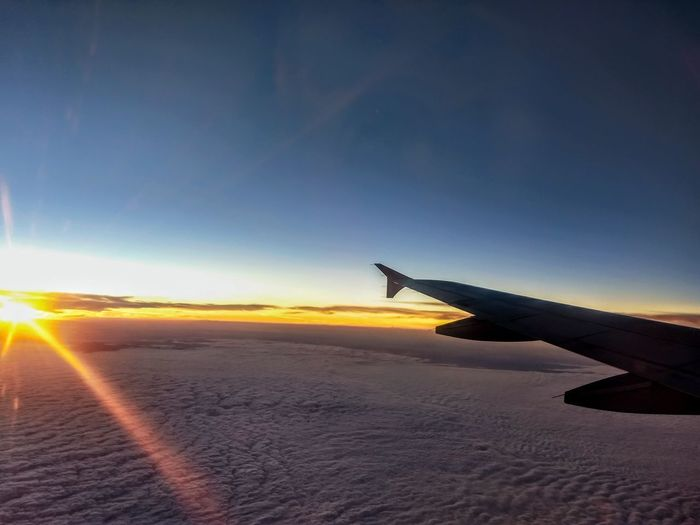 Airplane flying over landscape against sky during sunset