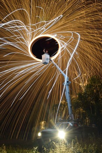 Low angle view of man spinning wire wool on cherry picker at night