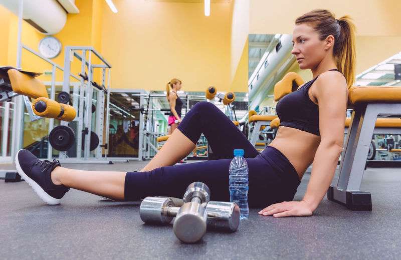 Beautiful sporty woman resting sitting on the floor of fitness center and female friend doing exercises with dumbbells in the background Athletic Blonde Horizontal Sitting Woman Activity Club Dumbbell Equipment Female Fit Fitness Gym Healthy Lifestyle Indoors  Muscles Muscular Real People Resting Sport Train Training Water Weight Workout