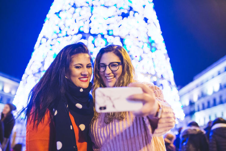Smiling young women taking selfie while standing against illuminated lighting outdoors