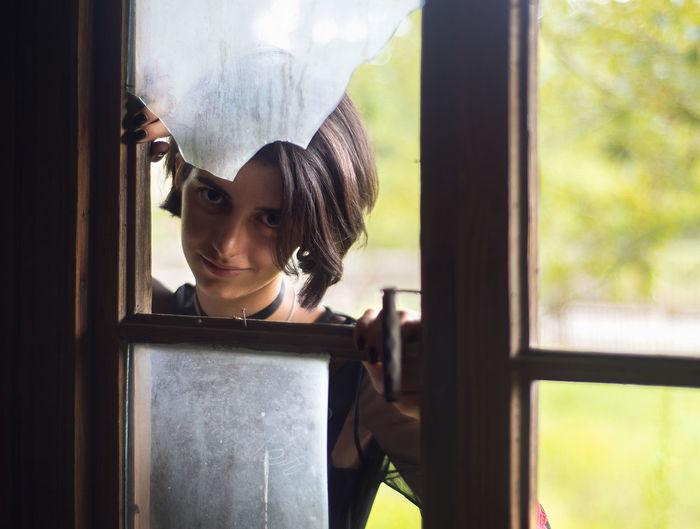 Portrait of young woman seen through broken window