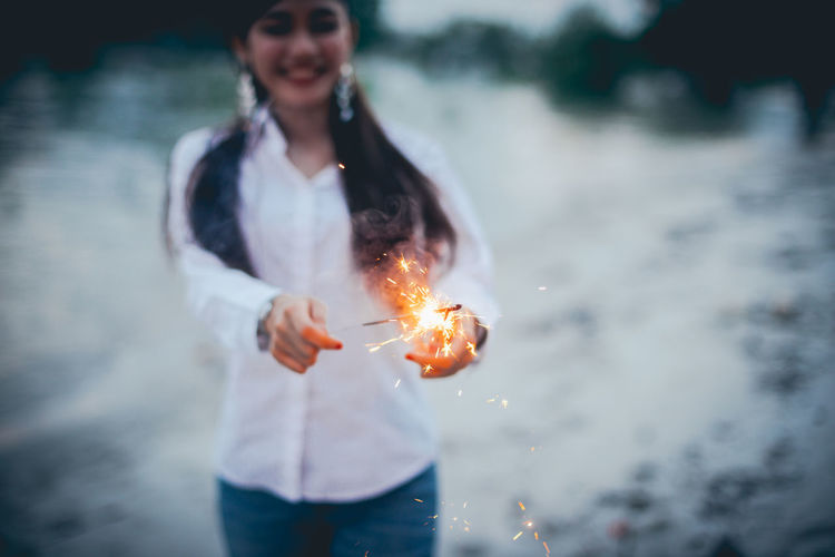 Adult Burning Casual Clothing Day Focus On Foreground Front View Hairstyle Holding Leisure Activity Lifestyles Motion Nature One Person Outdoors Real People Sparkler Standing Three Quarter Length Water Women