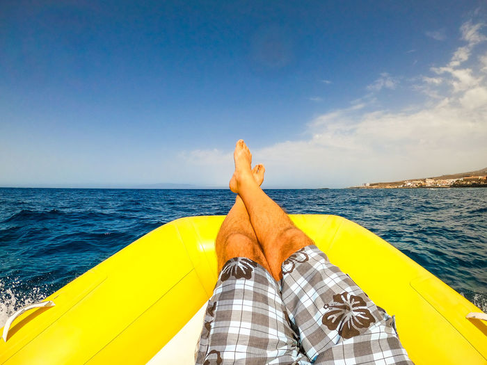 Low section of man relaxing on pool raft over sea against sky