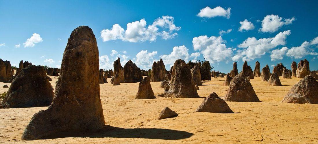 Rocks on desert landscape against cloudy sky