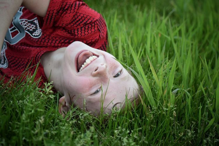 Grass Mouth Open One Person Lying Down Childhood Outdoors Day Nature Real People Leisure Activity Boys Headshot Happiness Smiling Close-up Child Human Body Part Children Only Young Women Young Adult The Portraitist - 2017 EyeEm Awards The Great Outdoors - 2017 EyeEm Awards Youth Of Today Children Happiness