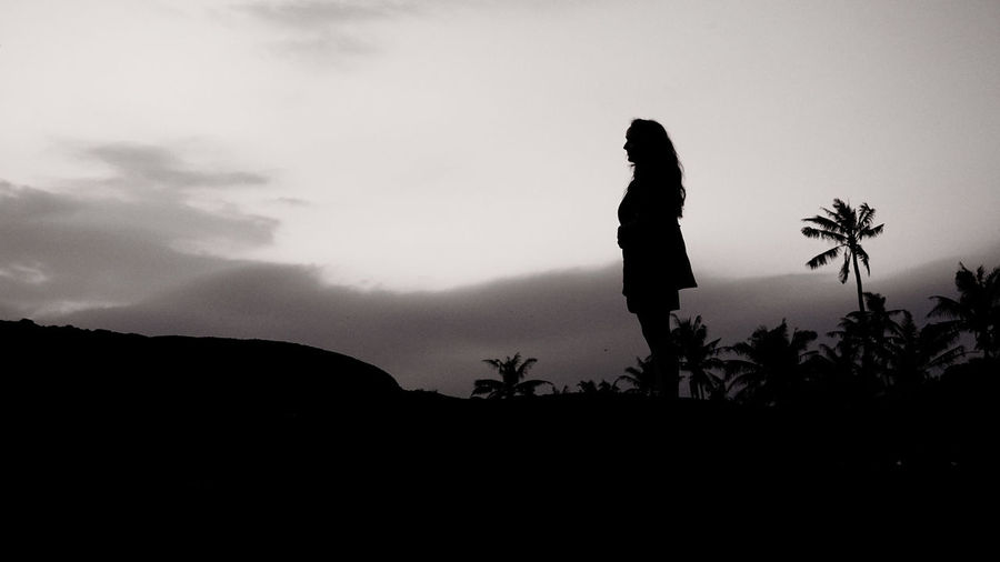 Silhouette man standing on rock against sky