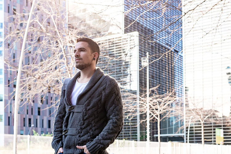 Young man looking away against buildings in city