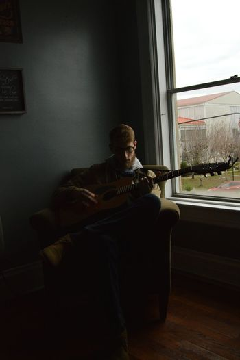 A moody musician. Musician Musical Instrument Guitar Guitarist Acoustic Guitar Hipster Plaid Contemplative Dark New Apartment Empty Places Winter Fall Cold Weather Lowlight Low Light Evening Relaxed Solitude Sitting Window Women Looking Through Window Window Sill RainDrop Curtain Thoughtful Living Room Cozy Drapes  Cushion Floor Lamp Home Sweet Home Window Frame The Portraitist - 2019 EyeEm Awards