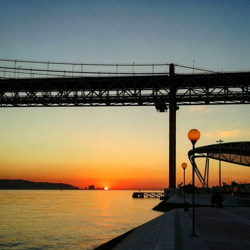 Sunset in Lisbon. Sunset Sea Water Bridge - Man Made Structure Beauty In Nature 25aprilbridge Ponte 25 De Abril Lisboa Portugal Pordodosol Dramatic Sky Sky Outdoors Sun No People Nature Day