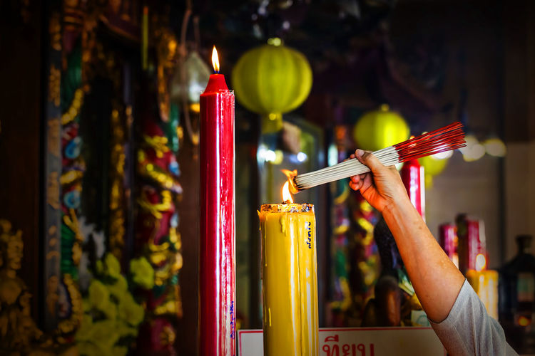 Cropped hand of person lighting incense sticks at temple