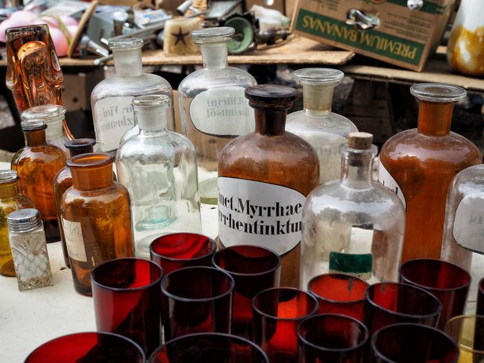 Glass bottles for sale on table in flea market