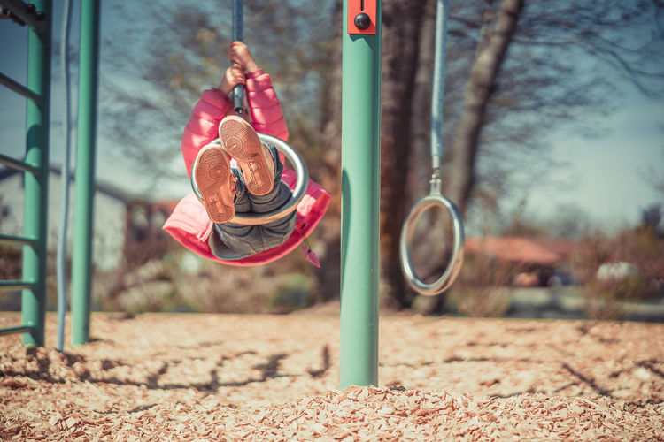 Full Length Of Playful Girl Wearing Warm Clothing While Swinging At Playground